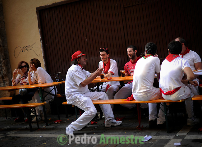 Participants eat the street during the San Fermin Festival, on July 10, 2012, in Pamplona, northern Spain. The festival is a symbol of Spanish culture that attracts thousands of tourists to watch the bull runs despite heavy condemnation from animal rights groups . (c) Pedro ARMESTRE