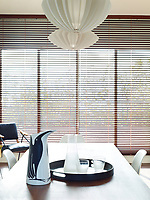 In the dining room, pendant lights with retro style shades hang above a wood dining table; a jug and tray with glassware stand on the table. The floor to ceiling window is dressed with wood venetian blinds.