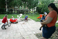 Foster parent Bobbi Pedersen, right, finishes feeding her foster child Kareem Craycraft as her adopted daughter Aleah Pederson, left, chases foster child Christopher Gray around their back patio Monday June 16, 2003 in Columbus, Ohio.<br />