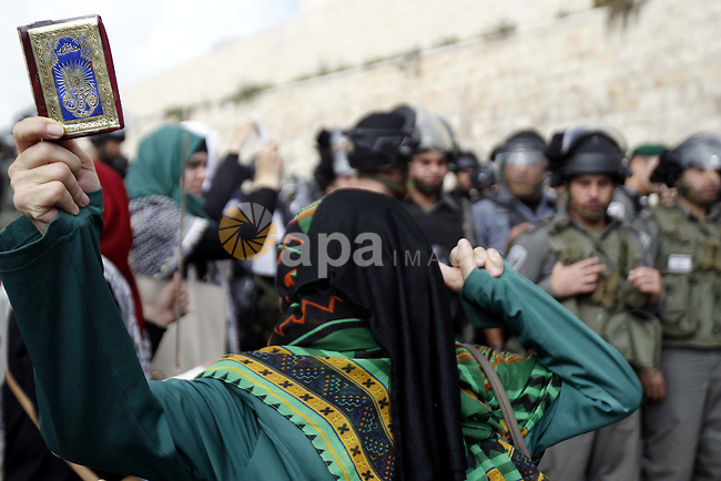 Israeli security forces stand next to a Palestinian woman shouting slogans during a rally near the entrance of al-Aqsa mosque compound to protest after authorities restricted access to the esplanade on October 15, 2014 outside Jerusalem's Old City. For the second time in a week, authorities allowed only Palestinians aged over 50 to enter. Four Palestinians were arrested and three police were injured during clashes that followed the protest, police spokeswoman Luba Samri said. Photo by Muammar Awad