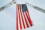 American flag suspended between ladder trucks for fire fighter's funeral.