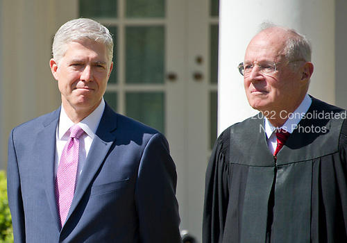 Associate Justice of the United States Supreme Court Neil Gorsuch, left, and Associate Justice Anthony Kennedy, right, listen as US President Donald J. Trump makes remarks at the ceremony where Gorsuch will take the Oath of Office in theRose Garden of the White House in Washington, DC on Monday, April 10, 2017.<br /> Credit: Ron Sachs / CNP<br /> (RESTRICTION: NO New York or New Jersey Newspapers or newspapers within a 75 mile radius of New York City)