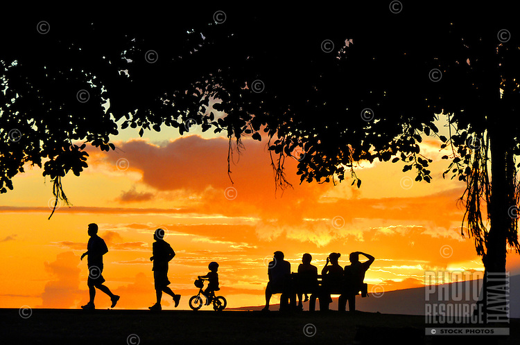 A brilliant sunset is the backdrop as locals and visitors enjoy Magic Island at Ala Moana Beach Park, O'ahu.