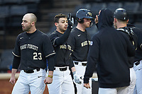 Patrick Frick (5) of the Wake Forest Demon Deacons is greeted by his teammates after scoring a run against the Illinois Fighting Illini at David F. Couch Ballpark on February 16, 2019 in  Winston-Salem, North Carolina.  The Fighting Illini defeated the Demon Deacons 5-2.  (Brian Westerholt/Four Seam Images)