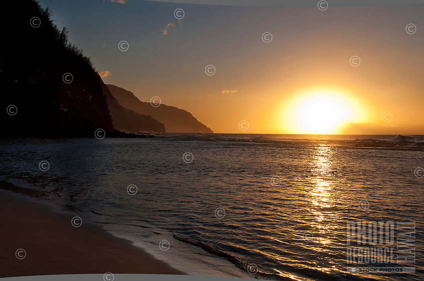 The setting sun casting a warm glow over the cliffs of Na Pali and the Pacific ocean off Ke'e Beach, Kauai.