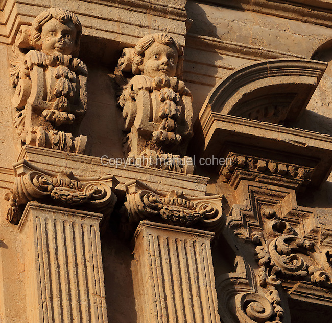 Architectural detail of the Baroque facade of an apartment building with pillars and Ionic capitals on the Corso Vittorio Emanuele, Noto, Syracuse, Sicily, Italy. Much of Noto was rebuilt after the earthquake of 1693 and the Sicilian Baroque style is therefore prevalent. Noto is listed as a UNESCO World Heritage Site. Picture by Manuel Cohen