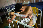 Abdul Rahim, 18, tries to rest in a burn unit at Mirwais Hospital in Kandahar, Afghanistan, April 23, 2009. Two months earlier, Rahim's clothing caught fire in his home in Shawali Kot District, Kandahar province. Afghans sometimes receive severe burns from fires used to heat their homes over the winter. Despite worsening security, development continues at Mirwais Hosptial, where the International Committe of the Red Cross conducts training and assists the local staff. Mirwais is the main public hosptial serving five southern provinces. As security has deteriorated in the South, many international NGO's have pulled their staff from the area or shut down the regional office, stunting development in a region where it is badly needed.