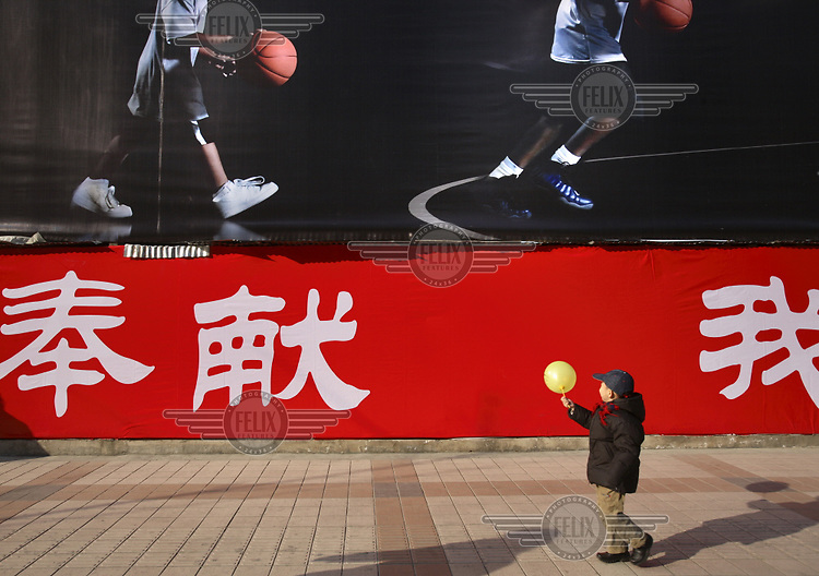 A child walks with a balloon beside a 2008 Olympic Games poster featuring young basketball players...