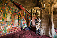 The priest shows off the amazingly colourful paintings at the Mikael Melehayzenghi rock hewn church.
