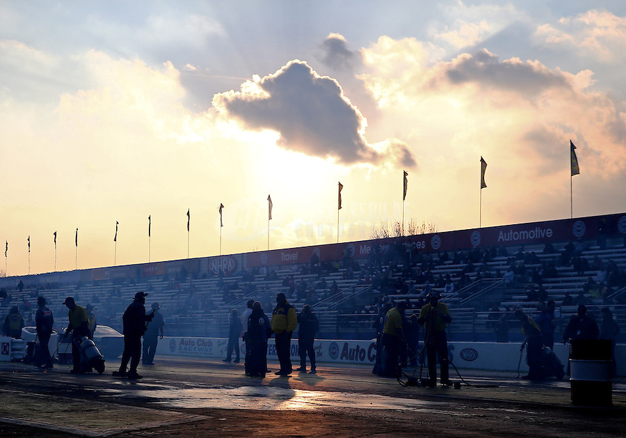 Feb 7, 2014; Pomona, CA, USA; NHRA personnel on the starting line as the sun sets behind the grandstands during qualifying for the Winternationals at Auto Club Raceway at Pomona. Mandatory Credit: Mark J. Rebilas-