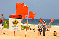 Spectators in the background obey surf warning signs at Sandy beach.