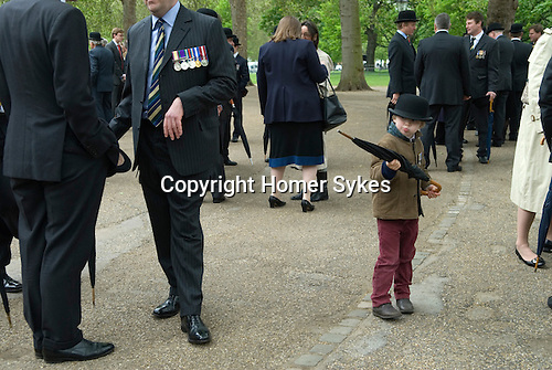 Combined Cavalry Old Comrades Association and parade, Hyde Park, London UK. Like father like son. A child uses his fathers umbrella as a pretend gun.