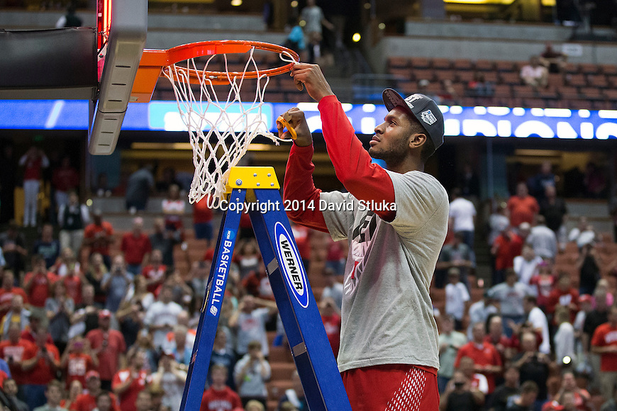 Wisconsin Badgers Vitto Brown cuts down a piece of the net after the Western Regional Final NCAA college basketball tournament game against the Arizona Wildcats Saturday, March 29, 2014 in Anaheim, California. The Badgers won 64-63 (OT). (Photo by David Stluka)