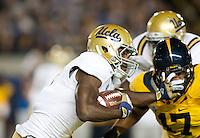 October 6th, 2012: UCLA's Johnathan Franklin stiff arms California's Brennan Scarlett during a game at Memorial Stadium, Berkeley, Ca    California defeated UCLA 43 - 17