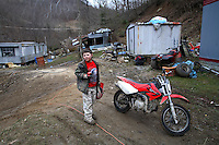 Zach Sturgill, 8, has benefited immensely from the foster grandparents reading scheme. Zach is at home surrounded by dilapatated trailer homes and his beloved motor bike.
