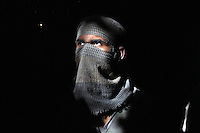 A worker stands in a shaft of light in a small informal leather factory. The dust produced from the manufacturing of products is damaging to the worker's health health hence they try to protect themselves with basic face scarves.