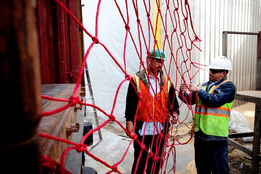 Los Angeles, California, March 1, 2010 - Daniel Torres, left, and Emilio Razo work to prepare a container for sugar beet pellets destined for Korea and Japan at the Los Angeles Harbor Grain Terminal. Demand for U.S. products is spiking in Asia, thanks to a weak dollar and quicker economic recovery. However, decline in U.S. consumption has left exports short of a good exit strategy. In 2009, imports fell 28%. This has created a bottleneck for exports, which need the shipping containers to move product overseas. ...