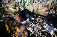"""A Honduran immigrant browses through a US porn magazine while waiting near the railroad track to climb up the cargo train known as 'La Bestia' (The Beast) in Lechería station, in the outskirts of Mexico City, Mexico, 6 November, 2014. Between 2010 and 2015, the US and Mexico have apprehended almost 1 million illegal immigrants from El Salvador, Honduras, and Guatemala. While the economic reasons remain the most frequent motivation for people from Central America to illegally immigrate to the US, thousands of Salvadorans, Guatemalans, and Hondurans, many of them minors, seek asylum in the US due to the thriving crime and gang-related violence in their region (known as the Northern Triangle). Taking an exhausting and risky journey, riding thousands of miles atop the cargo trains, facing a physical danger and extortion from the organized crime groups that control migrant routes, the """"undocumented"""" still flee to the US, looking for their American dream."""