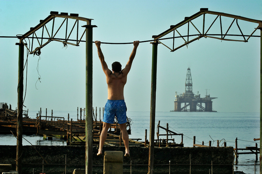 Baku, Azerbaijan, 14/10/2003..Man exercising on the beach in front of dilapidated SOCAR [State Oil Company of Azerbaijan Republic] oil fields......
