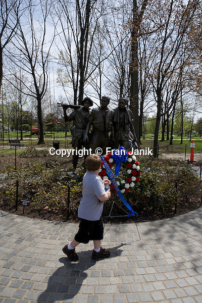 Located in the capitol city Washington DC, this statue depicting three U.S. foot soldiers is part of the memorial to the men and women lost during the Vietnam war. A boy walks by a wreath, on a sunny spring day.