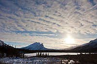 Clouds pattern the sky over the snow covered Mt Sukakpak and tundra pond in arctic, Alaska