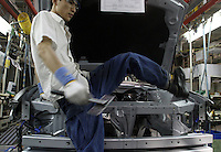 A Chinese worker gets out of the engine compartment after installing a component onto a Buick at the Shanghai General Motors (SGM) plant in Shanghai, China. SGM is a joint-venture between General Motors and the Shanghai Automotive Industry Corporation also known as SAIC..