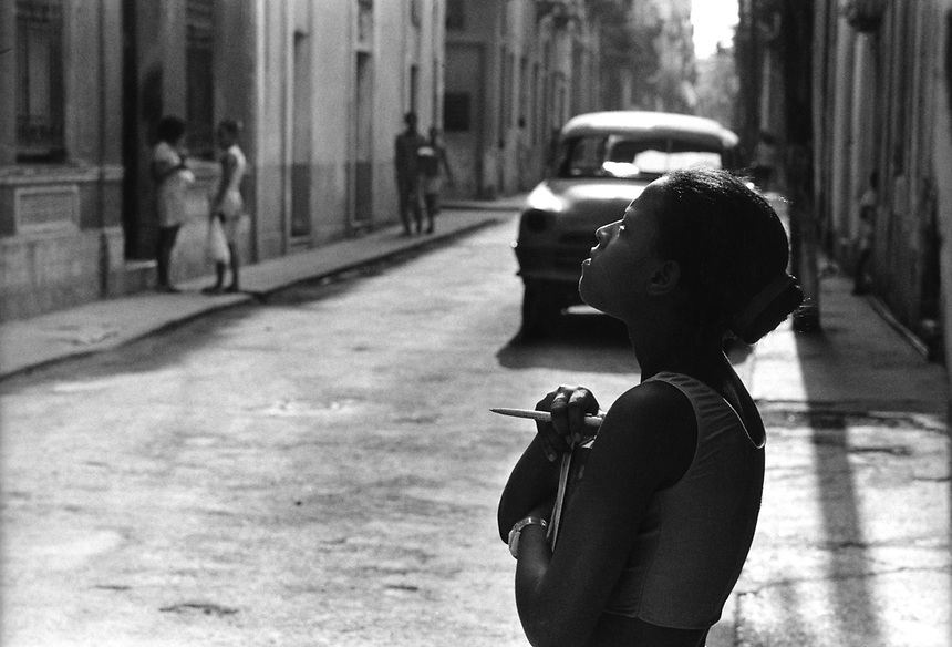 A young girl talks to a friend on a balcony above in Habana Vieja.