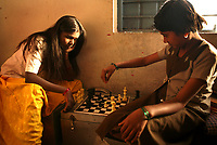 Malashri Kamble, 16 (left) and Saraswati Patil, 11, play chess at their hostel  at Vimochana Sangha's school for the children of Devadasis in Malabad, India.  Kamble's mother was a Devadasi who died at a young age and Kamble was recruited for the school by a social worker when she was 10 years old. The school, which was founded in 1990 by Mr. B.L. Patil, is the first residential school established to break the cycle of the Devadasi system.  Because the belief is that all female children of Devadasis should themselves become Devadasis, the school was created to remove the children from the culture in which this practice took place and instead offer them an education.  All students receive free tuition, books, uniforms, food and medical care. Graduates have gone on to become teachers, nurses, engineers etc. Kamble's grandmother has reservations about Kamble continuing with her studies.