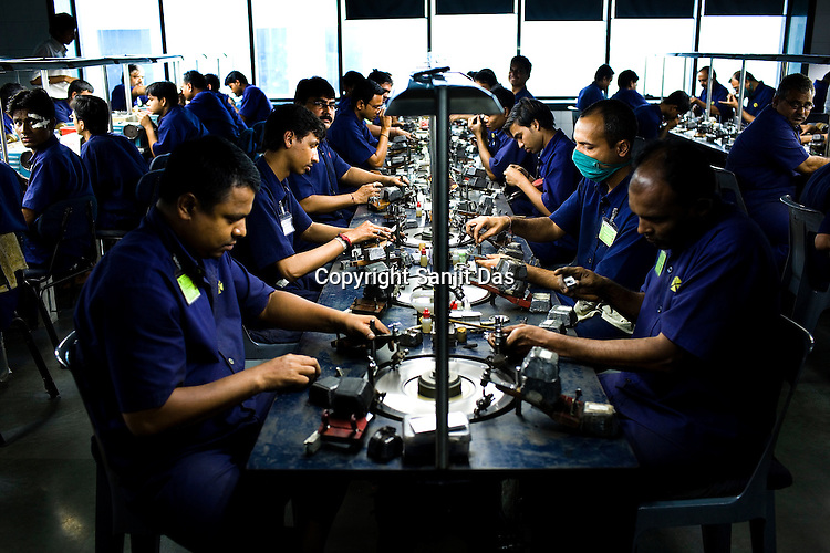 Diamond specialists are seen working on the diamonds at the diamond cutting and polishing factory in Surat, Gujarat, Western India.