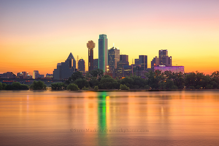 """Dallas Skyline at Sunrise"" – Gleaming like a sparkling gem, the early morning sun envelops the Dallas skyline in incandescent warmth with colors of aureolin, saffron, lavender, wisteria, and marigold. In the foreground, a flooded Trinity River winds past the city, revealing a rarely photographed moment of the beautiful Dallas skyline. (Photo/Stephen A. Masker)"
