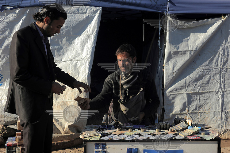 A money changer sitting at his stall in the Kawergosk Syrian Refugee Camp.