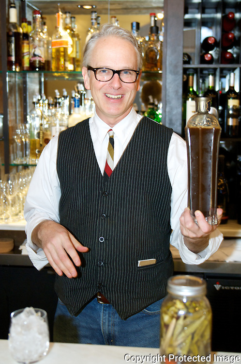 Bart Mallard is the mixologist at Acre Restaurant in Memphis. He's holding an infusion he made with moonsine.