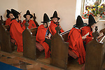 Old Ladies of Castle Rising. The Hospital of the Holy and Undivided Trinity Almshouses, Castle Rising, Norfolk, England 2007. Founders Day. The ladies wear tradiotional red cloaks and pointed black hats. Service in the chapel.
