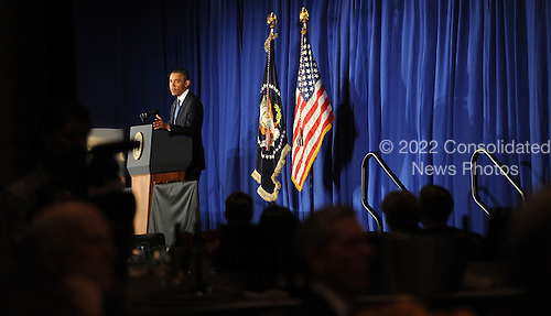 United States President Barack Obama reflects in a mirror as he speaks at the Business Council dinner February 27, 2013 at the Park Hyatt Hotel in Washington, DC. .Credit: Olivier Douliery / Pool via CNP