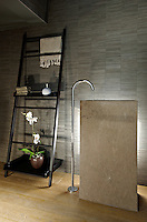 A contemporary grey tiled bathroom with a tall floor mounted tap fitting. A houseplant and other items are displayed on a black wood ladder shelf.