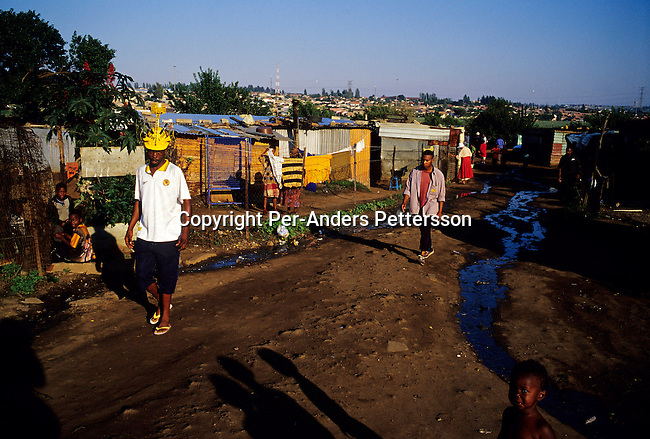 SOWETO, SOUTH AFRICA - FEBRUARY 19: Unidentified people walking along Joe Slovo, a poor area on February 19, 2004 in Soweto outside Johannesburg, South Africa. The government promised to build one million houses during the election in 1994 and about 1,7 million houses have been built. Still the housing backlog are estimated to about 6-7 million units, making it still a dream for many poor people in South Africa to own a house. .(Photo: Per-Anders Pettersson/Getty Images).....