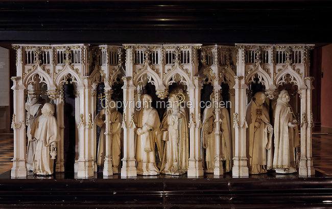 Facade of weepers under Gothic canopies by Claus Sluter, 1340-1405, and Claus de Werve, 1380-1459, on the tomb of Philippe le Hardi, or Philip the Bold, 1342-1404, (Philippe II, duc de Bourgogne, or Philip II, Duke of Burgundy), 1381-1410, in the Grande Salle du Palais des ducs de Bourgogne, or Salle des Gardes, a 15th century Flamboyant Gothic hall, in the Musee des Beaux-Arts de Dijon, opened 1787 in the Palace of the Dukes of Burgundy in Dijon, Burgundy, France. The tomb consists of a painted alabaster effigy with lion and angels, and below, figures of pleurants or weepers among Gothic tracery. Claus Sluter worked on the weepers 1389-1404 and produced startlingly realistic sculptures, and Claus de Werve completed them 1404-10. The tombs were originally from the Chartreuse de Champmol, or Chartreuse de la Sainte-Trinite de Champmol, a Carthusian monastery which was sacked in the French Revolution and the tombs moved to Dijon cathedral then here in 1827. Picture by Manuel Cohen