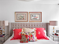 Close-up of the double bed with a collection of comfortable red and patterned cushions and a headboard upholstered in light stone coloured linen
