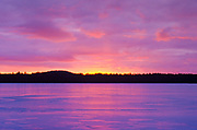 Sunset over Lake Massabesic in Auburn, New Hampshire USA during the winter months.