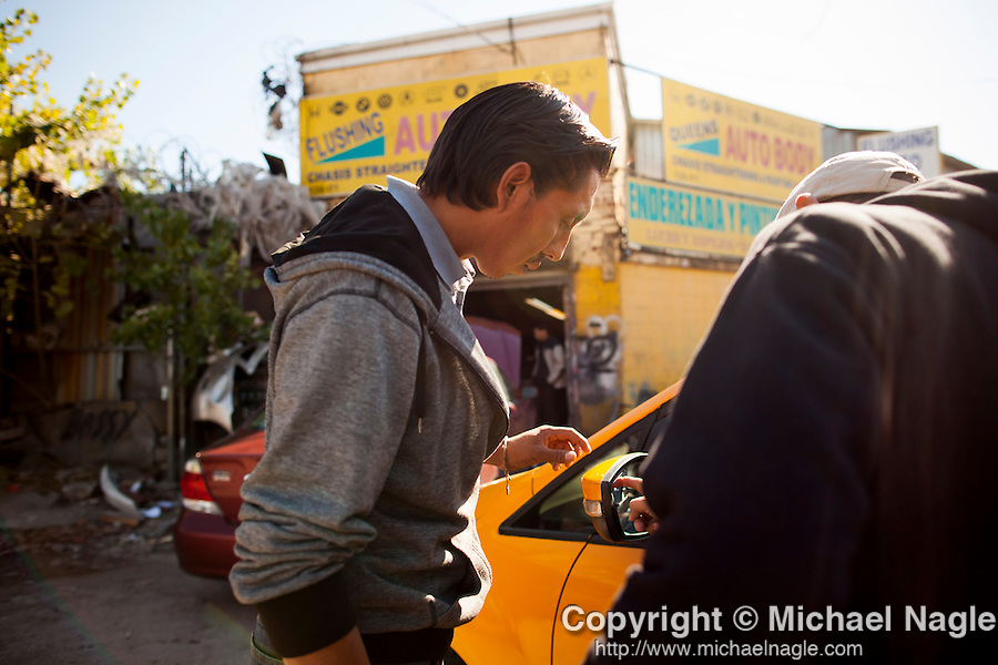QUEENS, NY -- OCTOBER 21, 2013:  Jose Hernandez, 32, talks with a taxi driver about options for fixing his broken mirror in Willets Point on October 21, 2013 in Queens.  Photographer: Michael Nagle for The New York Times