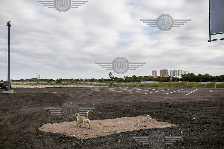 A dog walks across an area of asphalt which covers what were protected mangroves once thrived near the Olympic golf site. <br /> <br /> The authorities and private developers have poured billions of dollars into transportation projects, hotels, a residential complex to house the athletes and a vast Olympic Park where nearly half the sports will be played in Rio's expansive neighbourhood, Barra da Tijuca. <br /> <br /> Those improvements join the private schools, gated communities, and other consumer culture that attracts middle-class families tired of run-down feel of Rio's older neighbourhoods. <br />  <br /> However, the breakneck development has brought problems similar to those of which its new residents were fleeing, including congested traffic and untreated sewage in what was supposed to be a new model for urban living.