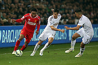 SWANSEA, WALES - MARCH 16: Jack Cork of Swansea (C) challenges Raheem Sterling of Liverpool (L)<br />
