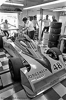 INDIANAPOLIS, IN: Dan Gurney (upper right, center) looks over his  Eagle 7700/Offenhauser TC driven by Pancho Carter during the Indianapolis 500 on May 29, 1977.