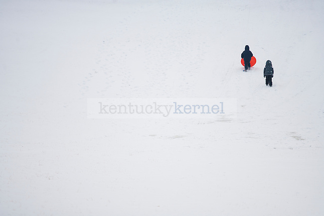 """Two kids climb up the hill in """"The Bowl"""" outside the William T. Young Library in Lexington, Ky.,on Monday, February 3, 2014. Photo by Michael Reaves 