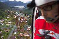 "Switzerland. Canton Ticino. Novaggio. A Rega Agusta AW109 SP Grand ""Da Vinci"" helicopter on its way to rescue an elderly man suffering from a heart problem. The doctor Michele Musiari looks through the window towards the town. All Rega helicopters carry a crew of three: a pilot, an emergency physician, and a paramedic who is also trained to assist the pilot for radio communication, navigation, terrain/object avoidance, and winch operations. The name Rega was created by combining letters from the name ""Swiss Air Rescue Guard"" as it was written in German (Schweizerische Rettungsflugwacht), French (Garde Aérienne Suisse de Sauvetage), and Italian (Guardia Aerea Svizzera di Soccorso). Rega is a private, non-profit air rescue service that provides emergency medical assistance in Switzerland. Rega mainly assists with mountain rescues, though it will also operate in other terrains when needed, most notably during life-threatening emergencies. As a non-profit foundation, Rega does not receive financial assistance from any government. The AgustaWestland AW109 is a lightweight, twin-engine, helicopter built by the Italian manufacturer Leonardo S.p.A. (formerly AgustaWestland, Leonardo-Finmeccanica and Finmeccanica). Leonardo S.p.A is an Italian global high-tech company and one of the key players in aerospace. In close collaboration with the manufacturer, the Da Vinci has been specially designed to cater for Rega's particular requirements as regards carrying out operations in the mountains. It optimally fulfills the high demands made of it in terms of flying characteristics, emergency medical equipment and maintenance. Safety, performance and space have been increased, and maintenance and noise emissions reduced. In the background, the Lake Lugano (Italian: Lago di Lugano or Ceresio) is a glacial lake which is situated on the border between southern Switzerland and northern Italy. 10.09.2017 © 2017 Didier Ruef"