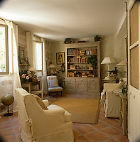 A country sitting room with  a terracotta tiled floor and painted stone walls. A sofa and an armchair with neutral covers provide the seating. Books and other items are displayed in a freestanding bookcase.