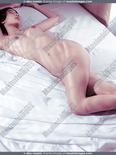 Artistic nude photo of a young asian woman sleeping naked on white bed sheets