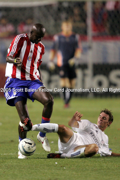 22 July 2005: New England's Andy Dorman (on ground) tackles the ball away from CD Chivas's Ezra Hendrickson. CD Chivas USA defeated the New England Revolution 1-0 at the Home Depot Center in Carson, California in a Major League Soccer regular season match.