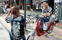 China. Province of Zhejiang. Hangzhou. Two young men sit on their lightweight motor cycles parked on the sidewalk . One of the teenagers wears a tee shirt with the face of John Lennon. © 2004 Didier Ruef