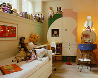 Every surface of this girl's bedroom, which is furnished with colourful and unusually shaped furniture, is covered in books and toys